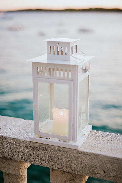 White metal lantern with burning candle glowing with sea in the background