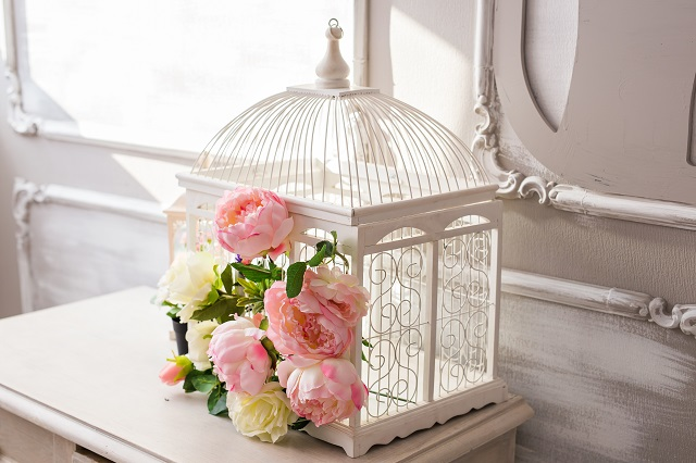 Shabby chic bird cage in interior. White cage