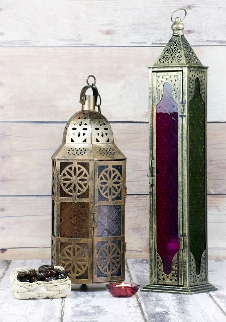 Glass and bronze coloured metal lanterns with candle and basket of dates